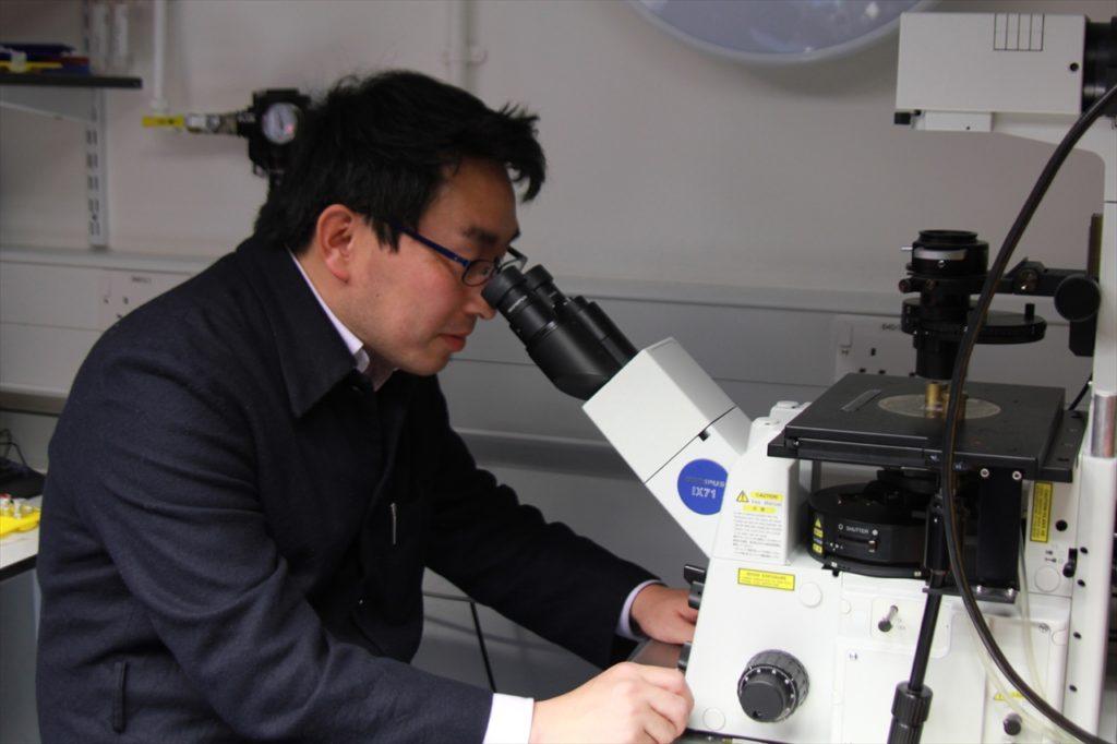 最新鋭の顕微鏡を手にする松島博士